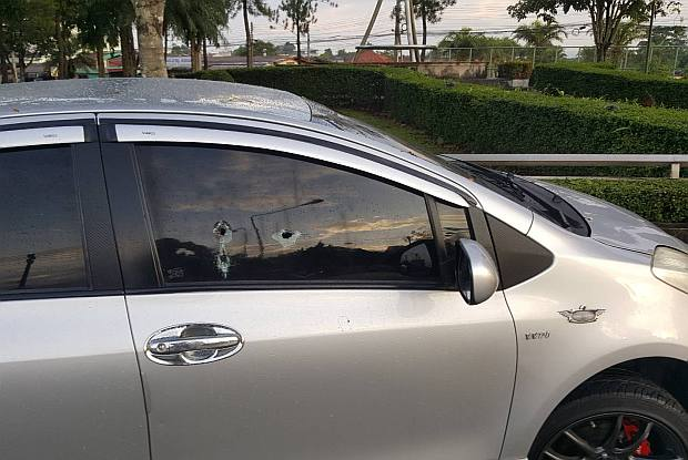 Bullet holes can be clearly seen on the side window of the car driven by a woman  who was shot dead by her husband, who then killed himself, in front of the wife's daughter while they were travelling home together early on Monday night.(Photo by Waedao Harai)