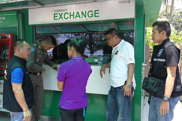 An 18-year-old hotel maid arrested for stealing money from a Russian tourist's room is taken to the currency booth where she exchanged the US banknotes for baht, during a re-enactment of the crime on Tuesday. (Photo: Pattaya tourist police)