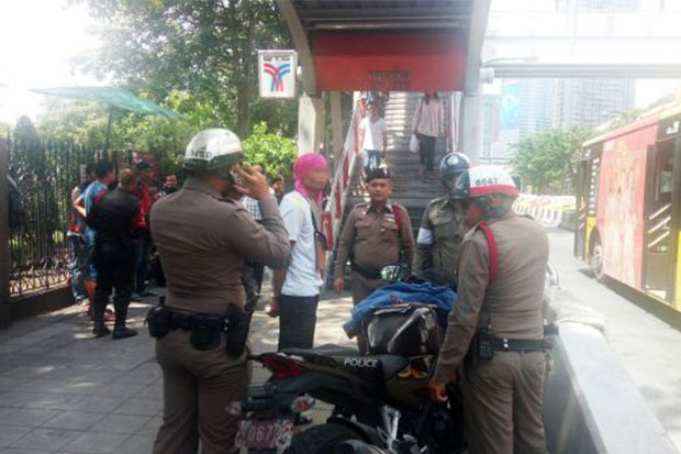 Attacker Winai Homniam, 41, with a red towel wrapped around his head, in police custody after a German tourist was slashed along the side of the neck near Mor Chit BTS station in Bangkok on Tuesday. (Photo taken from JS100.com)