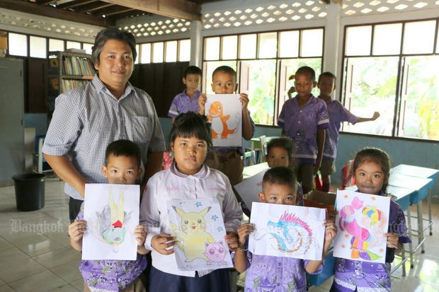 Teacher Suphab Sukcharoen has students show off their drawings. Mr Suphab, 36, will be the only teacher at Nean Samhor School in Phichit's Muang district after his senior colleague retires at the end of this month. (Photo by Sittipot Kaebui)