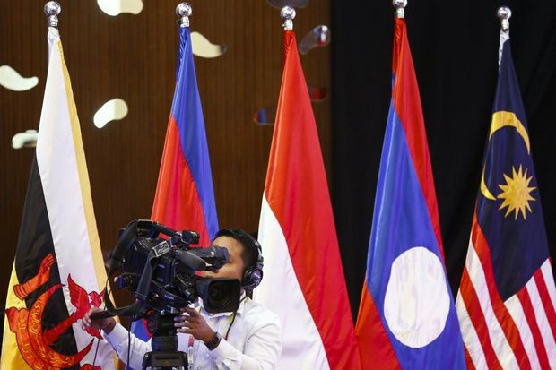 A cameraman operates alongside flags of the Asean countries during a meeting of economic ministers last year in Pasay City, near Manila. (EPA file photo)