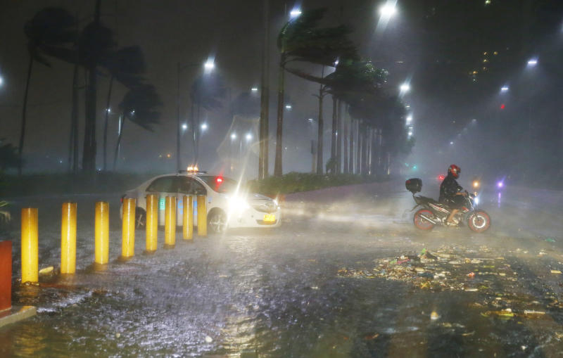 Motorists avoid a flooded street as heavy rains and strong winds brought about by Typhoon Mangkhut barrelled into northeastern Philippines before dawn Saturday. (AP photo)