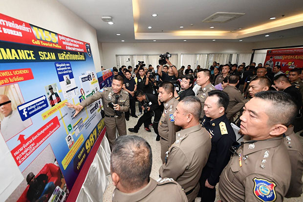 Pol Maj Gen Surachate Hakparn, deputy commissioner of the Tourist Police Bureau, points to a chart outlining the workings of the romance scam network at a news conference on Saturday. (Tourist Police Bureau photo)