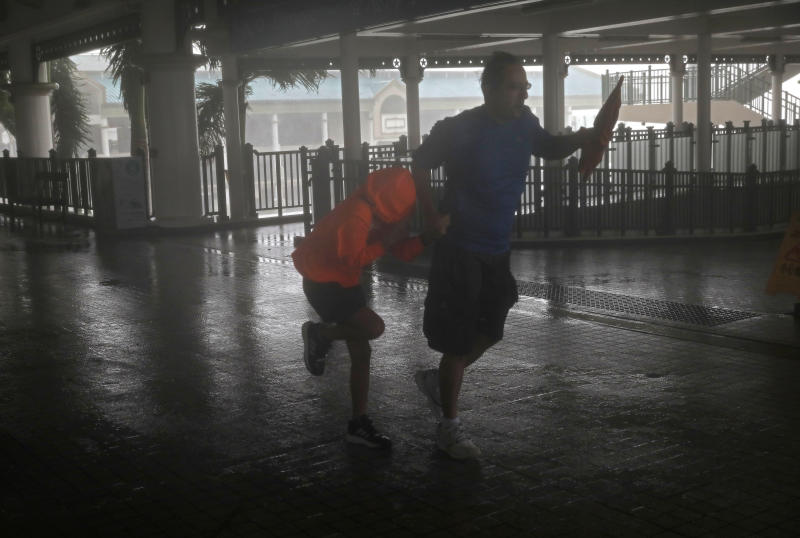 A man and a girl battle strong winds from Typhoon Mangkhut on a pier on Victoria Habour in Hong Kong on Sunday. (AP photo)