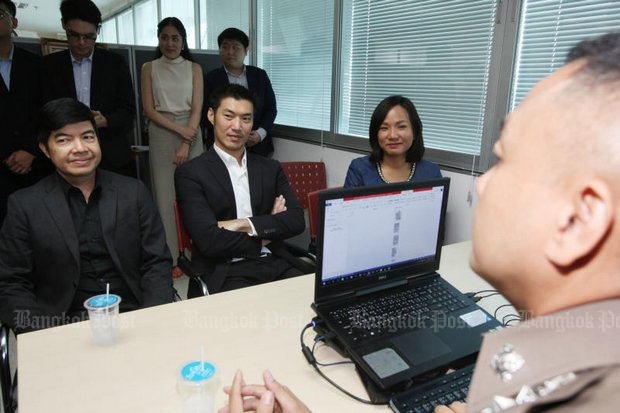 Future Forward leader Thanathorn Juangroongruangkit (centre) and two other party executive members, Klaikong Vaidhyakarn (left) and Jaruwan Sarankaet, meet technology crime suppression police on Monday. (Photo by Apichit Jinakul)