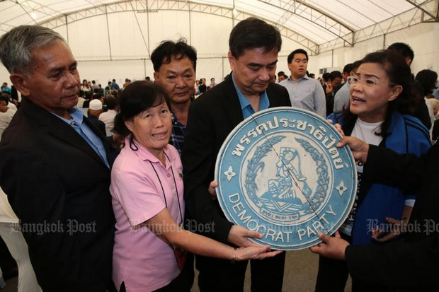Democrat Party leader Abhisit Vejjajiva (second from right, visiting party headquarters earlier this year) will face a confidence vote by all party members. (File photo by Wichan Charoenkiatpakul)