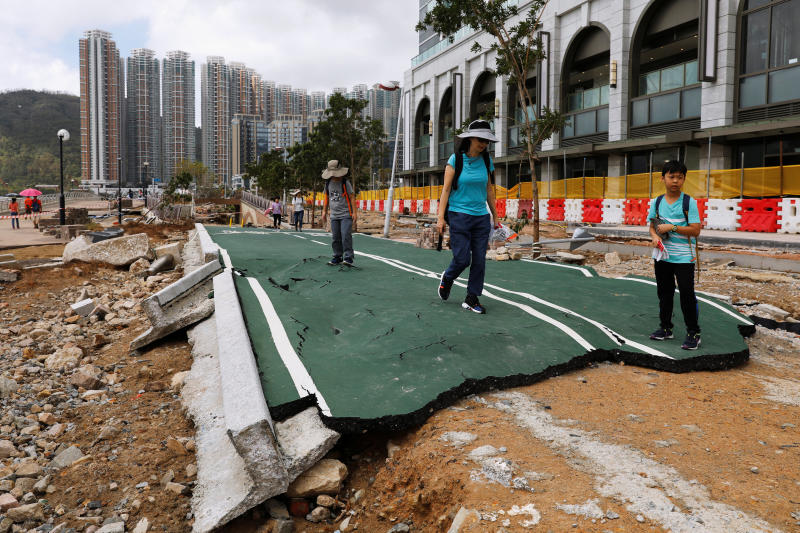 People walk through a damaged path on Tuesday after Super Typhoon Mangkhut hit Hong Kong. (Reuters photo)
