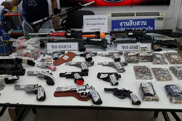 Eighteen weapons and almost 1,000 rounds of ammunition for various types of firearms were seized from a house of a 29-year-old man who is a nephew of the owner of a tobacco factory in Kanchanaburi. (Photo by Piyarach Chongcharoen)