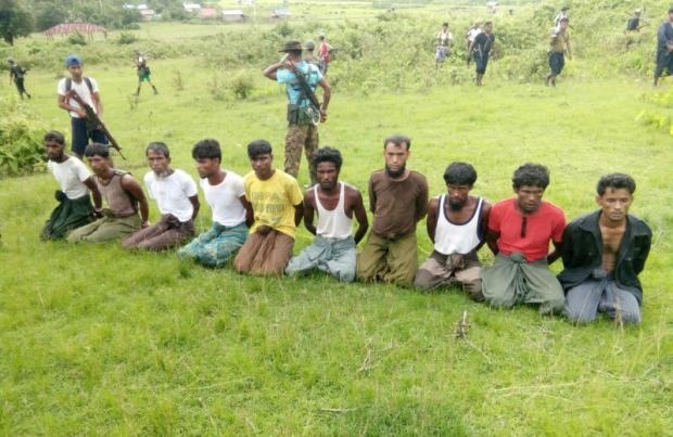 Ten Rohingya Muslim men with their hands bound kneel as members of the Myanmar security forces stand guard in Inn Din village Sept 2, 2017. Their bodies were later found in a mass grave. (Reuters file photo)