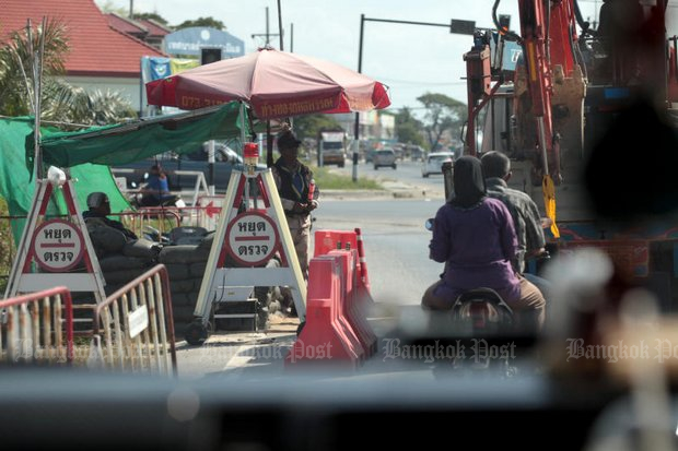 A couple on a motorcycle pass a heavily fortified checkpoint in Pattani. A new declaration of martial law in two villages of Pattani's Nong Chik drew protests from a youth group in the district - and a pro-army counter rally on Monday. (Bangkok Post photo)