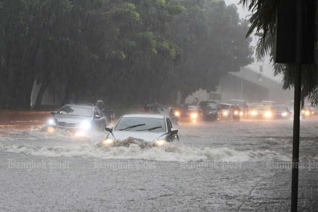 Motorists drive through heavy rain along flooded Praditmanutham Road in Bangkok last Sunday, when downpours hit several areas of the capital. And another soaking forecast for this weekend (File photo)