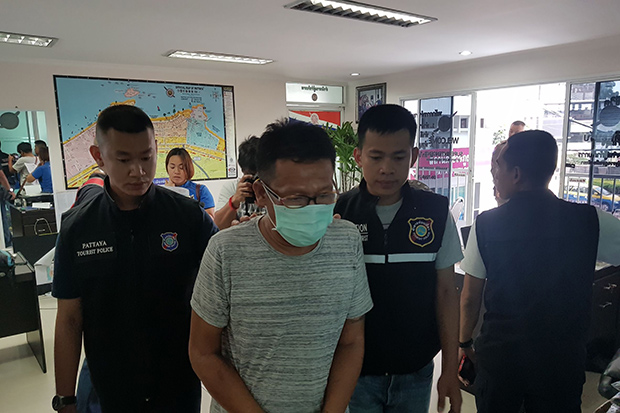 Bus driver Suchart Chanthachote is taken to the Pattaya police station on Monday on suspicion of stealing money from an American tourist and having crystal methamphetamine in possession. (Photo by Treenai Chansrichol)