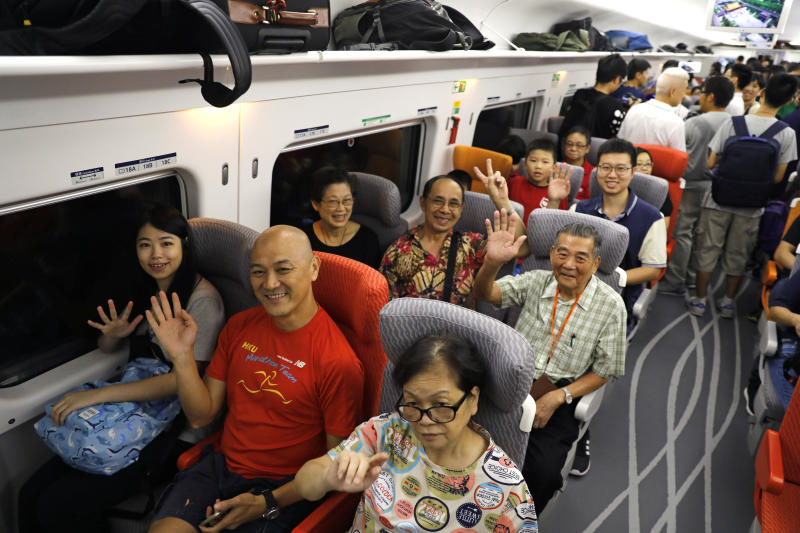 Passengers react on a first train departs from Hong Kong during the first day of service of the Hong Kong Section of the Guangzhou-Shenzhen-Hong Kong Express Rail Link in Hong Kong on Sept 23, 2018. (AP photo)