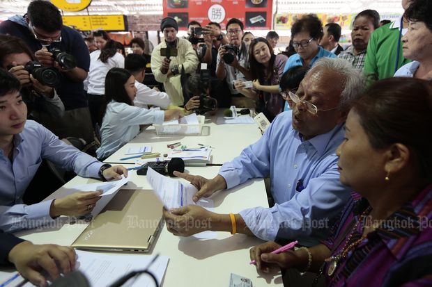 Mr Suthep (seated second from right) meets supporters at Pattavikorn Market in Bangkok's Bung Kum district on Monday. (Photos by Patipat Janthong)