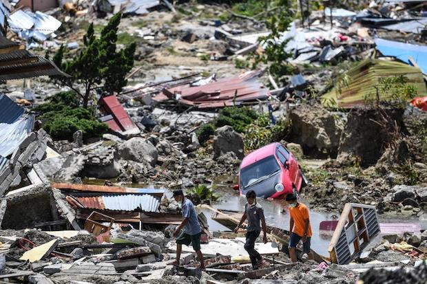Residents walk through debris in Perumnas Balaroa village in Palu, Indonesia's Central Sulawesi on Tuesday after an earthquake and tsunami hit the area on Sept 28. (AFP photo)