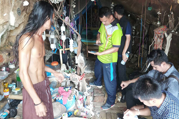 Authorities inspect the abode of Chatupoom Losiri (left), aka 'The Cave Man 2018', on Koh Phangan in Surat Thani. (Photo by Supapong Chaolan)