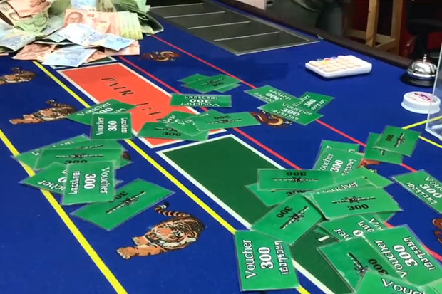 Many sets of gambling cards and other gambling equipment are seized during a military-led raid on a house-turned-gambling den in Chiang Mai's Muang district on Friday night in which 93 people are caught. (Video captured from @guruguroochiangmai Facebook page)