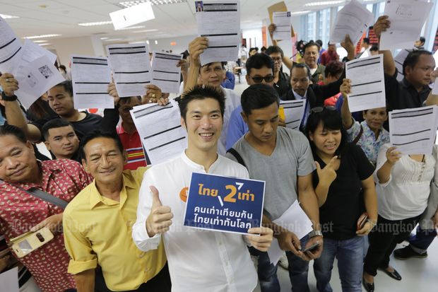 Future Forward Party leader Thanathorn Juangroongruangkit (front) poses with new members on the first day of registration in Bangkok on Saturday. (Photos by Wichan Charoenkiatpakul)
