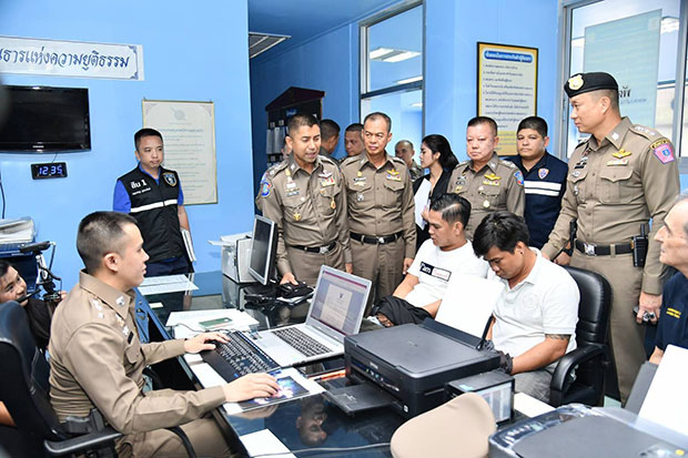 Pol Maj Gen Surachate Hakparn (standing, second from left), recently named to be the new Immigration Bureau chief, looks on as officers at Lumpini station question two Vietnamese men accused of robbing a German tourist. (Photo by the Tourist Police Bureau)