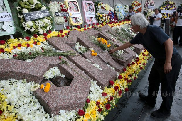 A man lays flowers at a memorial held to observe the 42nd anniversary of in the Oct 6, 1976 massacre at Thammasat University on Saturday. (Photos by Chanat Katanyu)