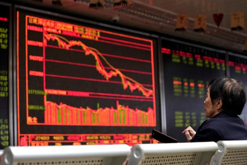 An investor watches a board showing stock information at a brokerage office in Beijing on Monday. (Reuters photo)