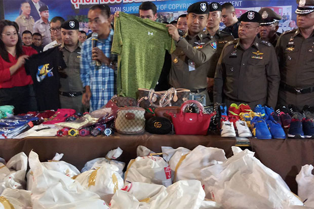 Pol Maj Gen Surachate Hakparn, acting chief of the Immigration Police Bureau, displays counterfeit goods seized during the raid on Save One Market, in downtown Korat, on Monday night, at a media conference on Tuesday.(Photos by Prasit Tangprasert)