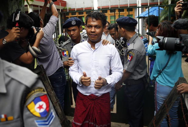 Chief reporter of Eleven media Phyo Wai Win (centre), escorted by police, gestures in handcuffs as he leaves Tamwe township courts before being brought to Insein Prison, Yangon, Myanmar, on Wednesday. (EPA photo)