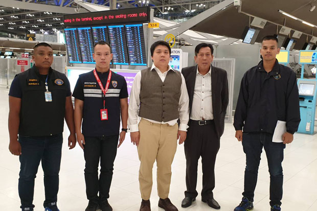 Prinya Jaravijit, 35, (centre) is arrested at Suvarnabhumi airport upon his return from the United States late on Wednesday night. He is the alleged mastermind of the 797 million baht bitcoin swindle. (Police photo)