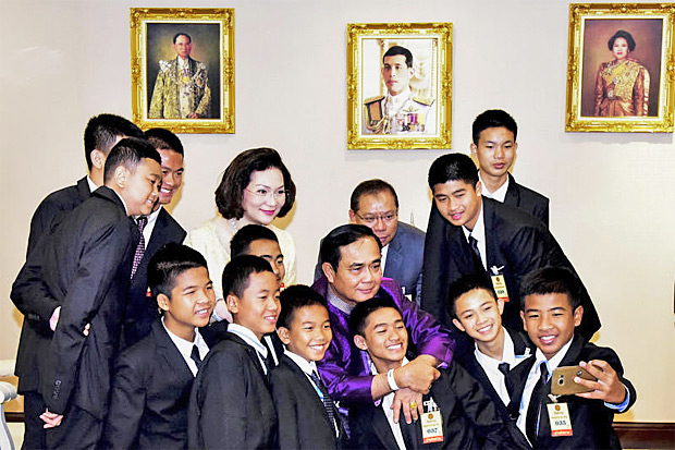 Prime Minister Prayut Chan-o-cha joins in a selfie photo with the Wild Boars footballers and their assistant coach, Tham Luang cave rescue chief Narongsak Osatanakorn and Khunying Pattama Leesawastrakul, at Government House on Tuesday. (Govt House photo)