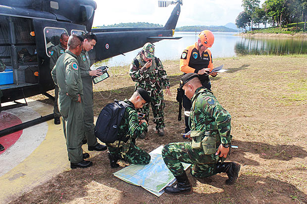 Soldiers study a map of the terrain where the tourist was lying injured after a fall on Monday, at Vajiralongkorn dam in Thong Pha Phum district on Wednesday. When the weather in the area finally lifts they planned to use the helicopter to take the man to hospital. (Photo: Piyarach Chongcharoen)