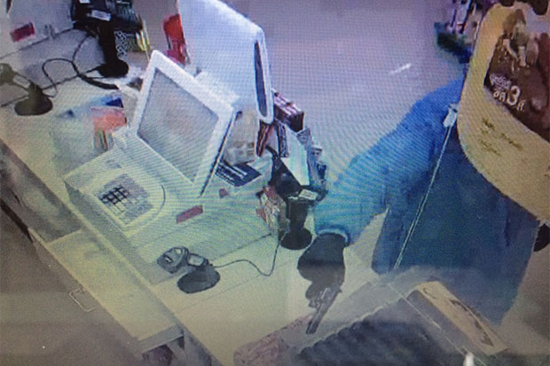 An armed man points a pistol at the staff at the counter of a 7-Eleven store in Muang district, Prachuap Khiri Khan, before fleeing with 8,000 baht in cash and a pack of baby diapers during a heavy downpour early Saturday morning. (Footage from the store obtained by Chaiyot Satyaem)