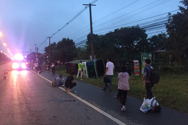 Uninjured passengers wait beside the overturned Sawaengwong Tour Co bus in Chatturat district in Chaiyaphum province sit for onward transport. Fifteen passengers and the driver were taken to hospital. (Photo by Makkawan Wannakul)