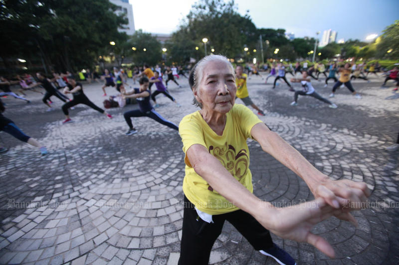 People take part in the evening aerobic exercise programme at Suan Santhiphap in Ratchathewi district on Monday. (Photo by Pornprom Satrabhaya)
