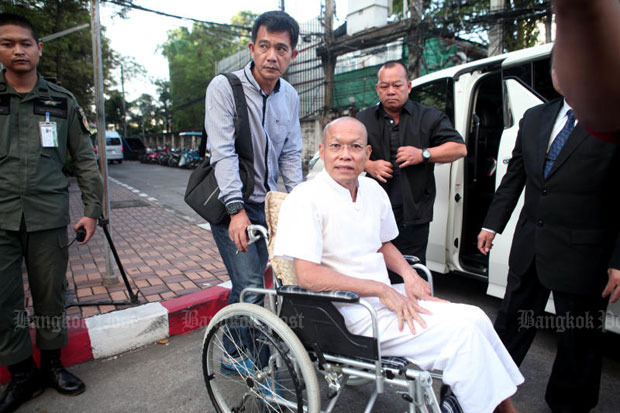 Suwit Thongprasert, formerly Phra Buddha Isara, arrives at the Criminal Court in Bangkok in a wheelchair on Monday for sentencing in the case involving the detention and assault of two plainclothes policemen during an anti-government protest he led in 2014. He was sentenced to 18-months in prison, suspended for one year.  (Photo by Apichart Jinakul)