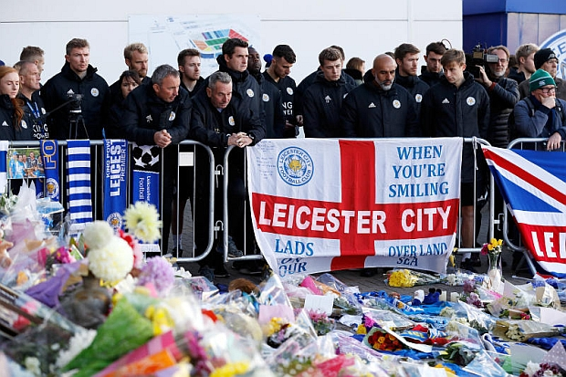 Members of Leicester City's staff look at tributes left outside Leicester City's King Power stadium, after the club's owner, Thai businessman Vichai Srivaddhanaprabha, and four other people died when the helicopter they were travelling in crashed as it left the ground after the match on Saturday, in Leicester on Monday. (Reuters photo)