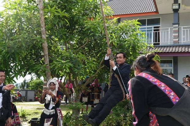 Prime Minister Prayut Chan-o-cha rides on a swing at Muang Ruang village in Chiang Rai during his mobile cabinet meeting in the province on Monday. (Government House photo)