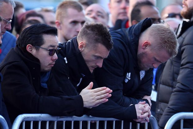 Aiyawatt 'Top' Srivaddhanaprabha, pays respect at the grieving site for his father in Leicester, England, alongside Leicester City striker Jamie Vardy and goalkeeper Kasper Schmeichel. (EPA photo)