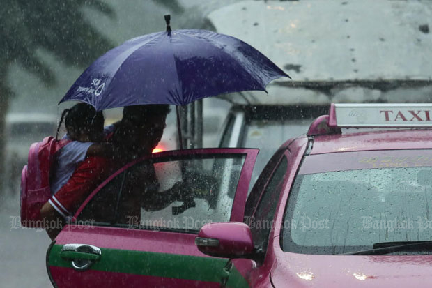 A man carrying a child tries to get a taxi in the rain in Bangkok. A new monthly flat rate service claims it will end the problem of cabbies rejecting fares. (File photo)