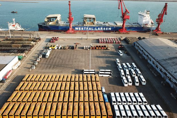 Buses and trucks to be shipped are seen in front of a cargo ship at a port in Lianyungang, Jiangsu province, China, on Wednesday. (Reuters photo)