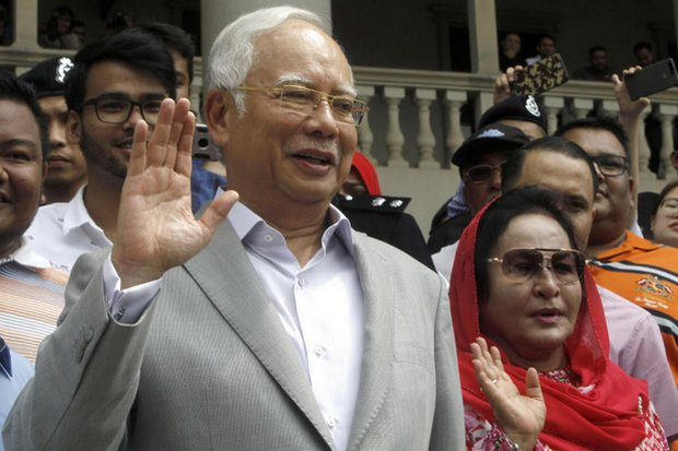 Former Malaysian Prime Minister Najib Razak and his wife Rosmah Mansor wave to a crowd outside the High Court in Kuala Lumpur in July. They both face multiple charges of corruption and money laundering. (AP file photo)