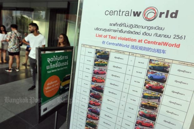 Passengers wait beside a board showing photos of taxis that have been subject of complaints by CentralWorld Shoppers for violating road regulations. The board is updated every month. (Photo by Wichan Charoenkiatpakul)