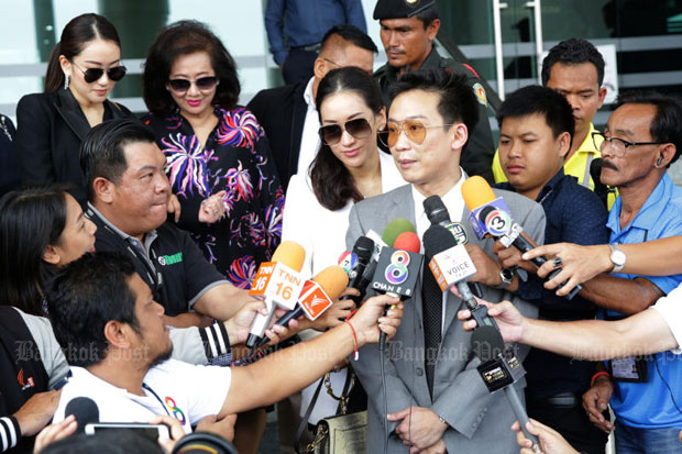 Panthongtae Shinawatra speaks to reporters at the Central Criminal Court for Corruption and Misconduct Cases in Dusit district in Bangkok on Monday, after he entered pleas of not guilty to money-laundering charges. Wearing dark sunglasses, from left, his sister Praethongtan, his mother Khunying Potjaman na Pombejra, and his sister Pinthongta accompany him. (Photo by Wichan Charoenkiatpakul)