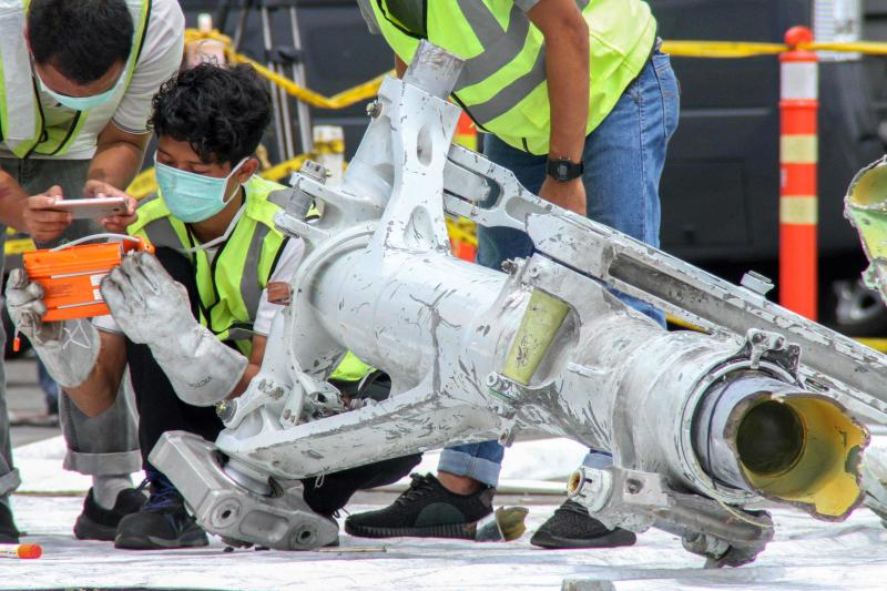 Lion Air investigators examine part of the landing gear of the ill-fated Lion Air flight JT610 at the port in northern Jakarta on Monday. (AP photo)
