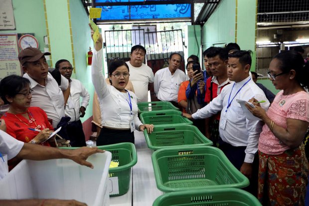 A Myanmar Election Commission staffer counts votes in the presence of poll monitors at a voting station in Yangon after one of the by-elections held on Saturday. (Reuters photo)