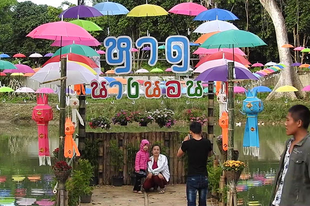 Visitors pose for a photo at Nang Non beach, decorated with colourful umbrellas, at the entrance to Khun Nam Nang Non-Tham Luang forest park in Chiang Mai's Mae Sai district. (Photo by Chinnapat Chaimol)