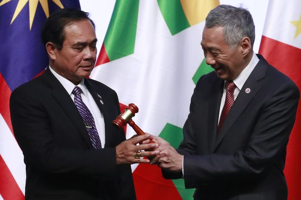 Prime Minister Prayut Chan-o-cha (left) receives the gavel from Singapore's Prime Minister Lee Hsien Loong (right) as a transfer of the Asean chairmanship during the closing ceremony of the 33rd Asean Summit and Related meetings in Singapore on Thursday. (EPA-EFE photo)