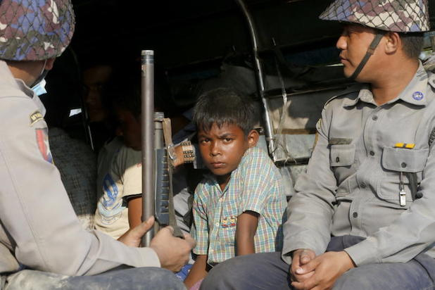 A boy looks from a police truck at the KyaukTan township, south of Yangon, Myanmar, on Friday. More than a hundred Rohingyas, including children and women believed to have fled the state of Rakhine, were arrested on a shore in KyaykTan township about 100 kilometres from downtown Yangon. (EPA photo)