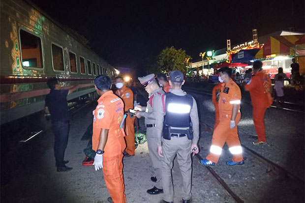 Police inspect the scene of a fatal crash in front of Huai Thalaeng railway station in Nakhon Ratchasima as rescue workers prepare to take the bodies of a 17-year-old girl and a 3-year-old boy killed by a special express train to a local hospital late Monday night. (Photo by Prasit Tangprasert)