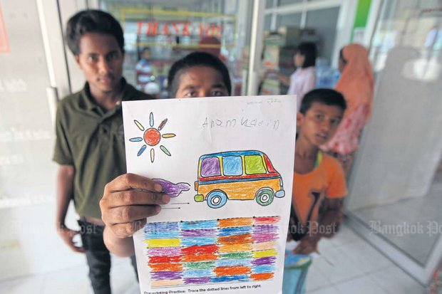 In this 2013 photo, a Rohingya boy shows his drawing at the Phangnga Shelter for Children and Families in Thailand. (Photo by Chumporn Sangvilert)