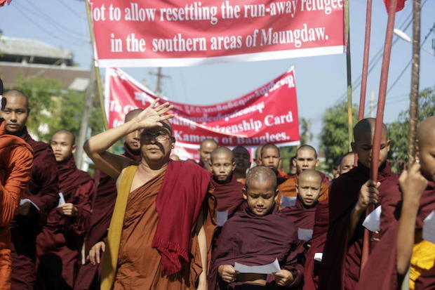 Rakhine Buddhist monks hold posters and placards during the protest in Sittwe, Rakhine State, Myanmar, on Sunday. (AFP photo).